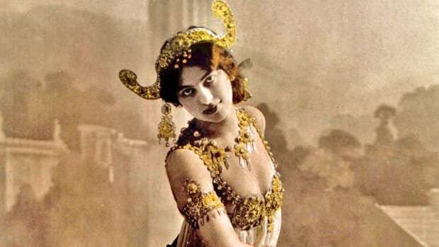 "Mata Hari, the archetype of the seductive female spy, is executed for espionage by a French firing squad at Vincennes outside of Paris. She first came to Paris in 1905 and found fame as a performer of exotic Asian-inspired dances. She soon began touring all over Europe, telling the story of how she was born in a sacred Indian temple and taught ancient dances by a priestess who gave her the name Mata Hari, meaning ""eye of the day"" in Malay. In reality, Mata Hari was born in a small town in northern Holland in 1876, and her real name was Margaretha Geertruida Zelle. She acquired her superficial knowledge of Indian and Javanese dances when she lived for several years in Malaysia with her former husband, who was a Scot in the Dutch colonial army. Regardless of her authenticity, she packed dance halls and opera houses from Russia to France, mostly because her show consisted of her slowly stripping nude. She became a famous courtesan, and with the outbreak of World War I her catalog of lovers began to include high-ranking military officers of various nationalities. In February 1917, French authorities arrested her for espionage and imprisoned her at St. Lazare Prison in Paris. In a military trial conducted in July, she was accused of revealing details of the Allies' new weapon, the tank, resulting in the deaths of thousands of soldiers. She was convicted and sentenced to death, and on October 15 she refused a blindfold and was shot to death by a firing squad at Vincennes."