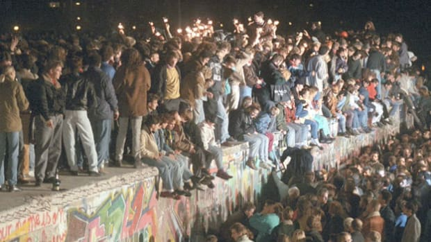 On the evening of November 9, 1989, East Germany announced an easing of travel restrictions to the west, and thousands demanded passage through the Berlin Wall. Faced with a growing demonstration, East German border guards allowed citizens to cross. CBS News is on the scene as scores of East Germans climb on top of the once-imprisoning wall.