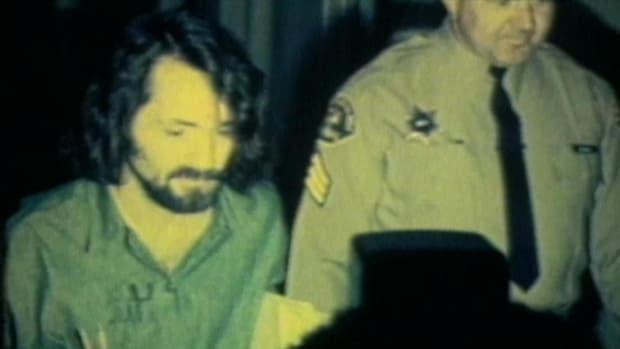 """Charles Manson and three female members of his """"family"""" (Leslie Van Houten, Susan Atkins, and Patricia Krenwinkel) are escorted down the halls of a courthouse after receiving guilty verdicts on multiple counts of murder in one of the most shocking cases in history."""