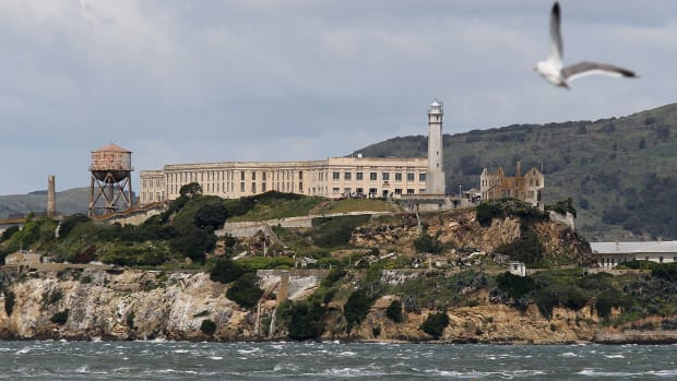 "On this day in 1934 Alcatraz opens its doors. A group of federal prisoners classified as ""most dangerous"" arrives at Alcatraz Island, a 22-acre rocky outcrop situated 1.5 miles offshore in San Francisco Bay. The convicts--the first civilian prisoners to be housed in the new high-security penitentiary--joined a few dozen military prisoners left over from the island's days as a U.S. military prison."