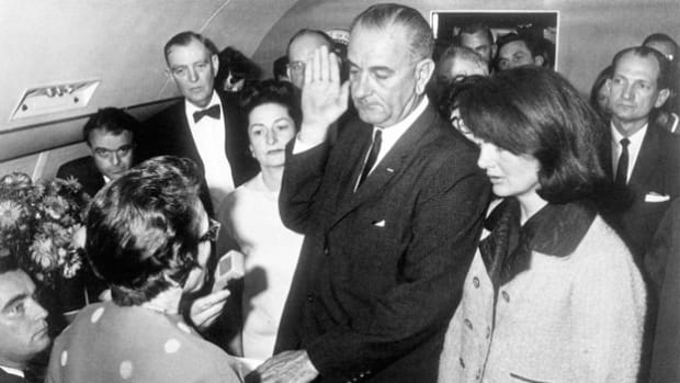 Following the assassination of John F. Kennedy on November 22, 1963, Vice President Lyndon B. Johnson is sworn in as president of the United States aboard Air Force One before the plane leaves Dallas for Washington, D.C.