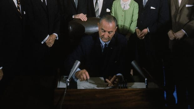 Newsreel footage of President Johnson signing the Voting Rights Bill.