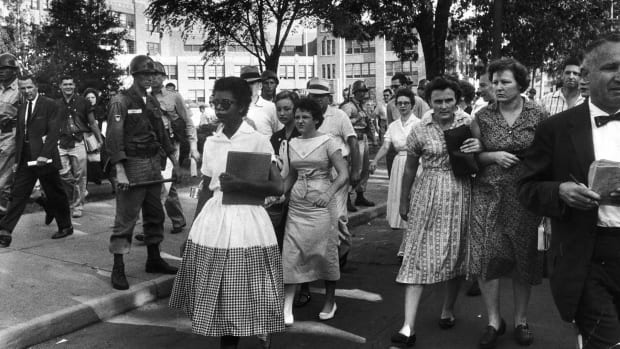 Under escort from the U.S. Army's 101st Airborne Division, nine black students enter all-white Central High School in Little Rock, Arkansas. Three weeks earlier, Arkansas Governor Orval Faubus had surrounded the school with National Guard troops to prevent its federal court-ordered racial integration. After a tense standoff, President Dwight D. Eisenhower federalized the Arkansas National Guard and sent 1,000 army paratroopers to Little Rock to enforce the court order.