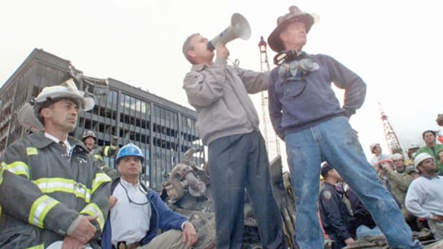On September 14, 2001, a day he declares a national day of mourning and remembrance, President George W. Bush stands atop a pile of rubble at Ground Zero and says that the terrorists responsible for the September 11 attacks will hear from America soon.