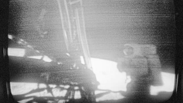 "On July 20, 1969, at 10:56 p.m. EDT, American astronaut Neil Armstrong, 240,000 miles from Earth, communicates with Mission Control as he takes ""one small step"" off the Eagle landing module and onto the moon."