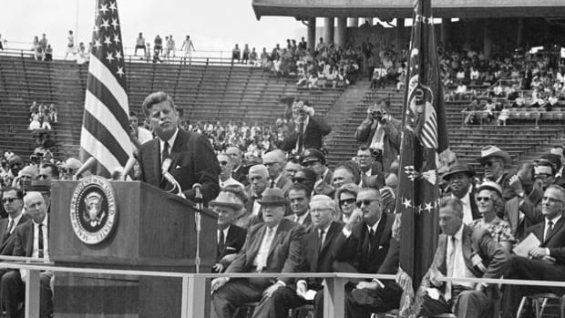 "In an address at Rice University on September 12, 1962, President John F. Kennedy rallies support for the race to space by telling his fellow Americans that the reason we endeavor to go to the moon is ""not because it is easy, but because it is hard."""