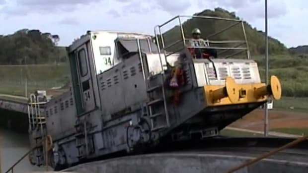 Powerful trains tow ships through the Panama Canal lock system.