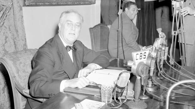 On December 29, 1940, in a radio broadcast to the United States, Europe and Japan, President Franklin D. Roosevelt heralds the defense program of the United States and urges Americans to support an increase in aid to Great Britain to help defeat the Axis powers.