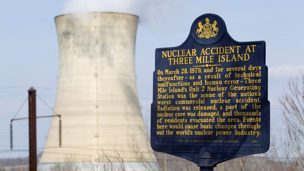 At 4 a.m. on March 28, 1979, the worst accident in the history of the U.S. nuclear power industry begins when a pressure valve in the Unit-2 reactor at Three Mile Island fails to close. Cooling water, contaminated with radiation, drained from the open valve into adjoining buildings, and the core began to dangerously overheat. After the cooling water began to drain out of the broken pressure valve on the morning of March 28, 1979, emergency cooling pumps automatically went into operation. Left alone, these safety devices would have prevented the development of a larger crisis. However, human operators in the control room misread confusing and contradictory readings and shut off the emergency water system. By early morning, the core had heated to over 4,000 degrees, just 1,000 degrees short of meltdown. The radiation levels, though not immediately life-threatening, were dangerous, and the core cooked further as the contaminated water was contained and precautions were taken to protect the operators. Finally, at about 8 p.m., plant operators realized they needed to get water moving through the core again and restarted the pumps. The temperature began to drop, and pressure in the reactor was reduced. Two days later, however, on March 30, a bubble of highly flammable hydrogen gas was discovered within the reactor building. The bubble of gas was created two days before when exposed core materials reacted with super-heated steam. On March 28, some of this gas had exploded, releasing a small amount of radiation into the atmosphere. After the radiation leak was discovered on March 30, residents were advised to stay indoors. Slowly, the hydrogen was bled from the system as the reactor cooled.