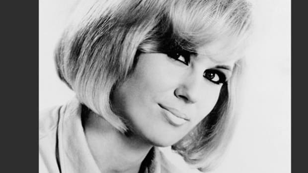 A news report describes the protest set off by British pop star Dusty Springfield when she refused to perform during a tour in South Africa unless she could sing to a non-segregated audience. Although her 1964 tour was cancelled, many other British rock stars joined her in condemning apartheid.