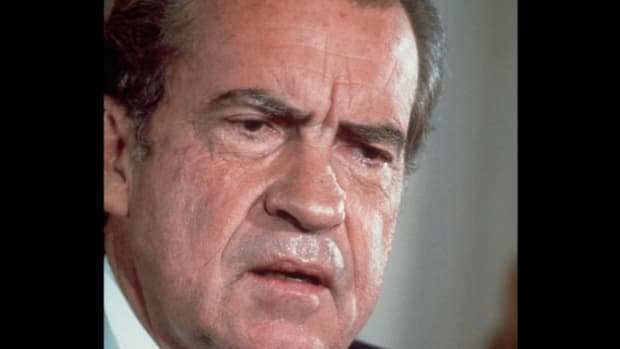 "On March 21, 1973, in a secretly recorded conversation, President Richard Nixon and his aide John Dean discuss the unfolding Watergate scandal. Dean tells Nixon that the cover-up is ""a cancer on the presidency."""