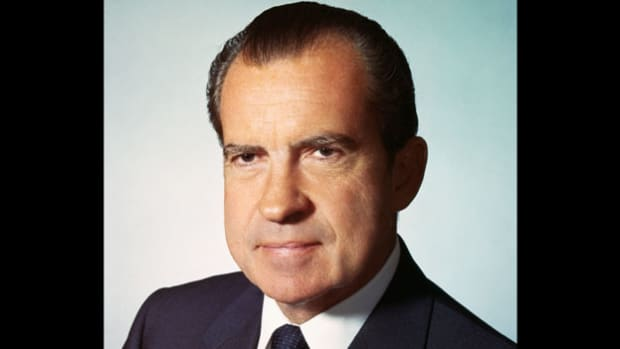 On March 26, 1971, President Richard Nixon holds a meeting in the Oval Office with his National Security Council to discuss the war in Vietnam. The meeting is secretly recorded. Among the many topics he raises, Nixon recounts a prior conversation with House majority leader Hale Boggs on setting a date for the final withdrawal of U.S. forces.