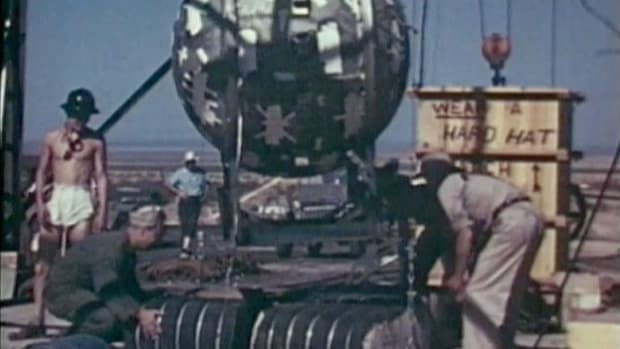 Watch actual footage of the first atomic bomb being prepared by U.S. engineers in 1945.