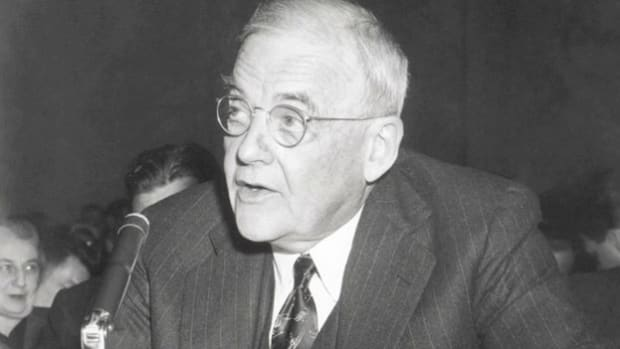 On February 24, 1956, Secretary of State John Foster Dulles addresses a Senate Committee assembled to discuss increasing tensions in the Middle East centered on Egypt's Suez Canal region.