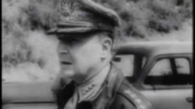 Witness General Douglas MacArthur arrive at New Guinea and a B24 plane bomb a Japanese cargo ship in this video from General MacArthur in World War II. In this latest video from the general, MacArthur arrives in New Guinea and is greeted warmly. MacArthur drives to the U.S. base on roads that were hacked out of the jungle. On the ride, he witnesses natives carrying supplies for the base, and the natives are protected by Australian troops. MacArthur introduces himself to some of the flyers, who are loading a B24 with bombs. The flyers are getting ready to take care of a Japanese cargo ship on the coast of New Guinea. Once over the ship, the video shows the men shoot the ship with machine guns, and then they drop a bomb on their target. The ship is crippled, and the American's mission is accomplished.