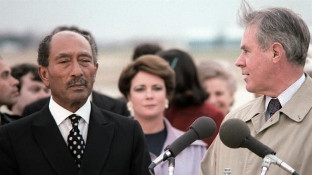 On October 6, 1981, Egyptian President Anwar el-Sadat was shot by Muslim extremists during a military parade commemorating the 1973 Yom Kippur War against Israel. In the first hours following the shooting, while Sadat lay in a hospital, the CBS News Bureau in Cairo tries to make sense of conflicting reports on whether the Egyptian leader had died.