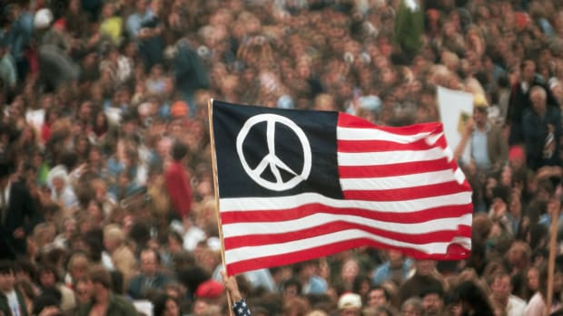 April 1971, Washington, DC, USA — A peace flag version of the American flag flies during a Vietnam War protest in Washington, DC. — Image by © Wally McNamee/CORBIS