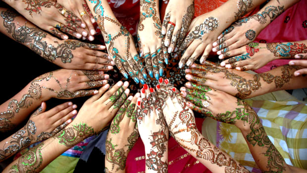 Pakistani girls show their hands decorated with Henna, ahead of the Muslims festival of Eid ul-Fitr, marking the end of holy Fasting month of Ramadan, in Multan Pakistan, on September 18, 2009. In Pakistan, mehndi is known more commonly as Henna. This is a plant whose leaves leave an impression on the skin—particularly palms and feet—of women very much like a tattoo. However, while the tattoo is permanent, Henna effects lasts about three to four weeks at best. The color varies from dark red to deep brown depending upon how long the henna is kept on the skin. Sometimes, addition of oil and lemon make the color darker and last longer. (Image by © MK CHAUDHRY/epa/Corbis)
