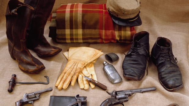 Assortment of Cavalryman gear includes boots, boot hook, blanket, spare shoes, kepi hat, gauntlets, French pin-fire pistols, a hoof knife, a leather cartridge case for pistol, a pair of hoof trimmers and a horse shoeing hammer. — Image by © Tria Giovan/CORBIS