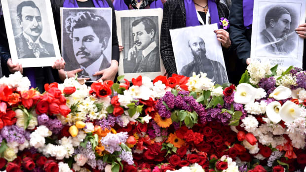 People holding photographs of (L-R) Armenian writer Krikor Zohrab, Armenian poet Ruben Sevak, Armenian poet Daniel Varoujan, Armenian priest and composer Komitas and Armenian writer Siamanto, who were among the Armenian intellectuals arrested by Ottoman forces in 1915, attend a flower laying ceremony at the Tsitsernakaberd Memorial, on April 24, 2015 in Yerevan, as part of the Armenian genocide centenary commemoration. Armenians on April 24 marked the centenary of the massacre of up to 1.5 million of their kin by Ottoman forces as France called on Turkey to recognise the 1915 slaughter as genocide. AFP PHOTO / KIRILL KUDRYAVTSEV