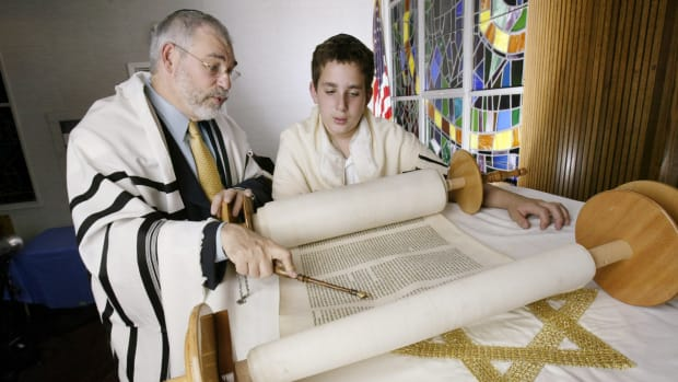 Dr. Pinchas Klein, left, rabbi of the Mount Freedom Jewish Center, views the Torah as he discusses the birth of Isaac on Rosh Hashanah in 2005.