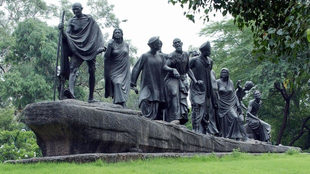 An Indian women takes a break from cleaning a statue which commemerates the Salt March of 1930 and features Indian leader Mahatma Gandhi (front statue R) leading a group of freedom fighters, in New Delhi, 10 August 2003.  India, which won its independence from the British rule in 1947, is preparing to celebrate the 56th anniversary of it's independence on 15 August.   AFP PHOTO/Jewel SAMAD  (Photo credit should read JEWEL SAMAD/AFP/Getty Images)