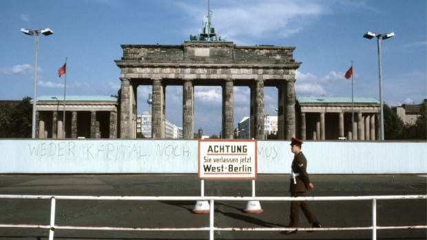 the-brandenburg-gate-in-east-berlin-in-the-front-the-wall-and-a-sign-with-the-writing-achtung-sie-verlassen-jetzt-west-berlin