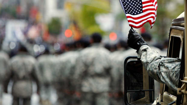 us-armed-serviceman-waves-american-flag-during-veterans-day-parade-in-new-york