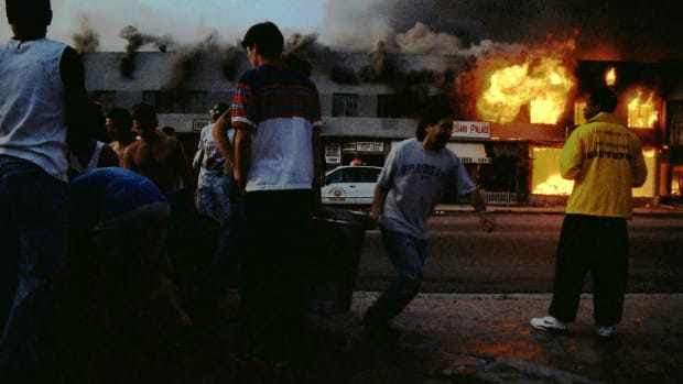 LOS ANGELES – April 30 – Rodney King Riot. Near intersection of Pico Boulevard and Hayworth Avenue, neighborhood residents filling buckets from open hydrant attempting to put out fires burning local businesses as the second night nears of riots that broke out after the policemen who beat Rodney King were found Not Guilty. April 30, 1992