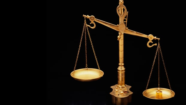 these-are-the-golden-scales-of-justice-they-represent-the-legal-system-and-courts-the-scales-here-are-shown-unbalanced-with-the-left-side-weighing-heavier-than-the-right-they-are-shown-against-a-bl