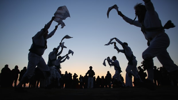 GLASTONBURY, ENGLAND – MAY 01:  Members of the Cam Valley Morris Men dance at a May Day dawn celebration in front of St. Michael's Tower on Glastonbury Tor on May 1, 2013 in Glastonbury, England. Although more synonymous with International Workers' Day, or Labour Day, May Day or Beltane is celebrated by druids and pagans as the beginning of summer and the chance to celebrate the coming of the season of warmth and light. Other traditional English May Day rites and celebrations include Morris dancing and the crowning of a May Queen with celebrations involving a Maypole.  (Photo by Matt Cardy/Getty Images)