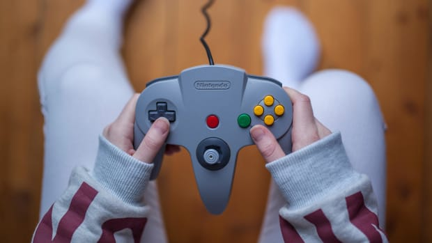 gothenburg-sweden-january-11-2015-a-young-womans-hands-holding-a-game-pad-controller-for-the-nintendo-64-video-game-console