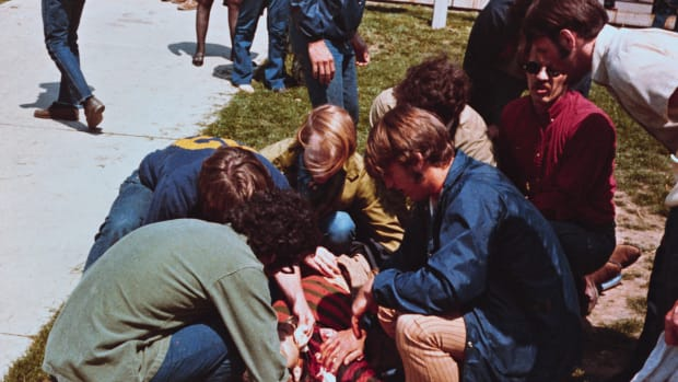 04 May 1970, Kent, Ohio, USA — Kent, Ohio:  Kent State University students demonstrate to protest the widening of the war in Southeast Asia.  National Guardsmen open fire on the 1,000 students and four fall dead, including two young women.  Eight others are wounded.  National Guardsmen are shown approaching a school building as students watch, a student is shown bleeding on the ground, and a student on a stretcher is wheeled to an ambulance. — Image by © Bettmann/CORBIS