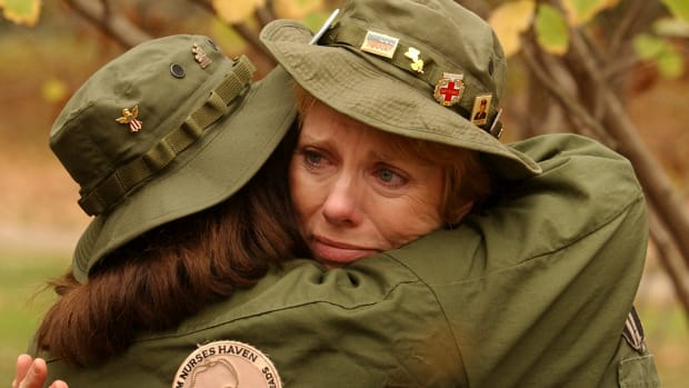 Carol Rogers Pitula of Chicago (facing camera) hugs fellow Army nurse Judy Baker Williams near the Vietnam Veteran's Memorial on Veteran's Day.