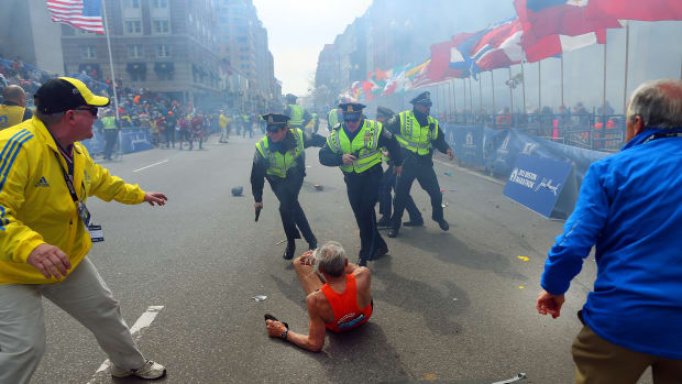 BOSTON – APRIL 15: Police officers with their guns drawn hear the second explosion down the street. The first explosion knocked down 78-year-old US marathon runner Bill Iffrig at the finish line of the 117th Boston Marathon. (Photo by John Tlumacki/The Boston Globe via Getty Images)