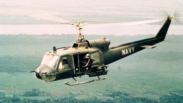 "23 Jan 1968 — Sighting the enemy, the door gunner aboard a ""Huey"" opens fire on a target below. UH-1B armed helicopters of Light Helicopter Attack Squadron THREE, Detachment 7, under the command of Lieutenant Commander William D. Martin, U.S.N., team up with Navy River Patrol Boats on search and destroy missions against Viet Cong positions in the Mekong Delta. — Image by © Bettmann/CORBIS"