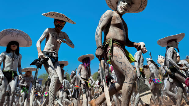 "JESÚS MARÍA, MEXICO – APRIL 21: Cora Indians, wearing scary demon masks, walk in a procession during the sacred ritual ceremony of Semana Santa (Holy Week) in Jesús María, Nayarit, Mexico, 21 April 2011. The annual week-long Easter festivity (called ""La Judea""), performed in the rugged mountain country of Sierra del Nayar, merges indigenous tradition (regeneration of life worshipping) and animistic beliefs with the Christian dogma. Each year, the Cora villages are taken over by hundreds of wildly running men. Painted all over their semi-naked bodies, fighting ritual battles with wooden swords and dancing crazily, they perform demons (the evil) that metaphorically chase Jesus Christ, kill him, but finally fail due to his resurrection. La Judea, the Holy Week sacred spectacle, represents the most truthful expression of the Coras' culture, religiosity and identity. (Photo by Jan Sochor/Latincontent/Getty Images)"