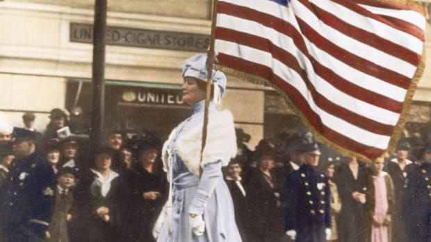 ca. 1914-1918, Manhattan, New York, New York, USA — Mrs. Herbert Carpenter, bearing an American flag, marches in a parade for women's suffrage on Fifth Avenue in Manhattan. — Image by © Bettmann/CORBIS