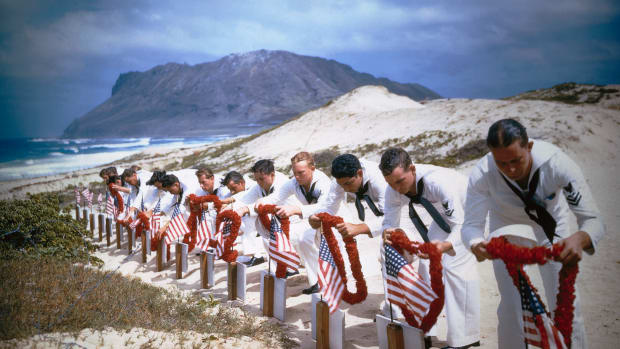 27 May 1942, Kaneohe, Oahu, Hawaii — Enlisted men of the Naval Air Station at Kaneohe, Hawaii, place leis on the graves of their comrades killed in the Japanese attack on Pearl Harbor last December 7th in this photo.  Graves were dug along the shore of the Pacific Ocean.  Diamond Head can be seen in the background. — Image by © Bettmann/CORBIS