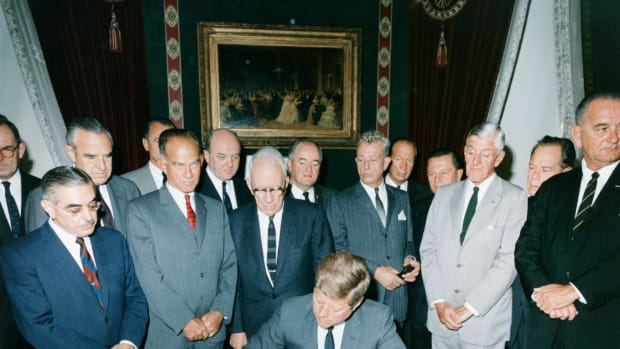 07 Oct 1963 — President Kennedy signs the Nuclear Test Ban Treaty in the White House Treaty Room with Vice President Lyndon B. Johnson and House and Senate members looking on.  October 7, 1963. — Image by © CORBIS