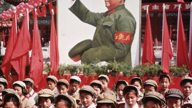circa 1968:  A group of Chinese children in uniform in front of a picture of Chairman Mao Zedong (1893 – 1976) holding Mao's 'Little Red Book' during China's Cultural Revolution.  (Photo by Hulton Archive/Getty Images)
