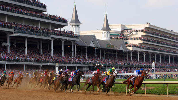 The field of 20 horses round the first turn during the 131st Kentucky Derby at Churchill Downs on Saturday, May 7, 2005.  Giacomo, riden by Mike E. Smith, is on the far left in the pink and green silks.
