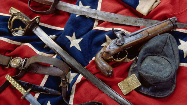 Civil War Confederate artifacts include a rare battleflag in mint condition, a C.S.A belt plate, and a very rare two-piece round buckle with belt. The top saber pictured is almost homemade, while the other is government issue. The kepi is also government issue, but the knife is not. The pistol was already a museum piece during the Civil War. — Image by © Tria Giovan/CORBIS