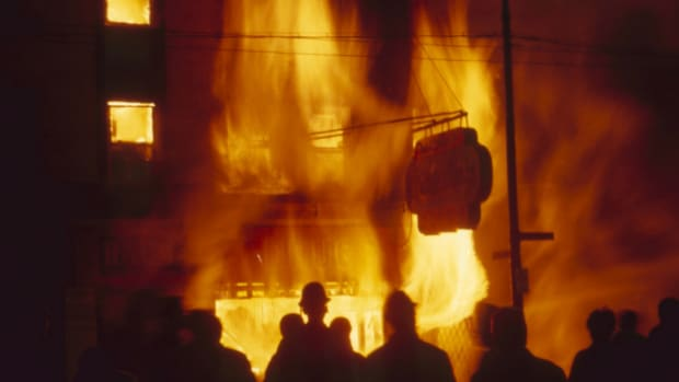 Onlookers watch as a Chicago storefront building burns during riots in the wake of Martin Luther King Jr's assassination, 1968. (Credit: Lee Balterman/The Life Picture Collection/Getty Images)