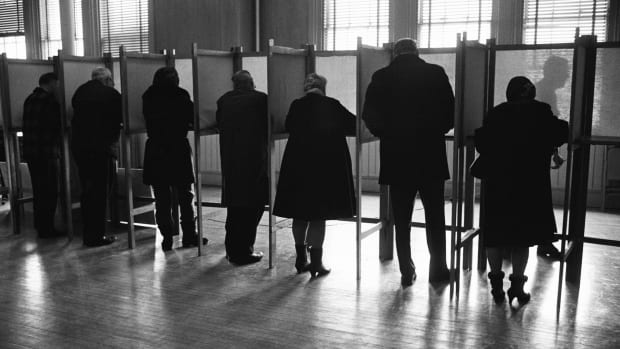 Circa 1970s: Men and women standing side by side in private voting booths, filling out election ballot papers.