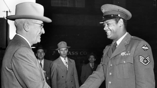 United States Air Force Staff Sergeant Edward Williams (right) of St. Louis, Missouri, exchanges a handshake with his Commander-in-Chief, President Harry S. Truman