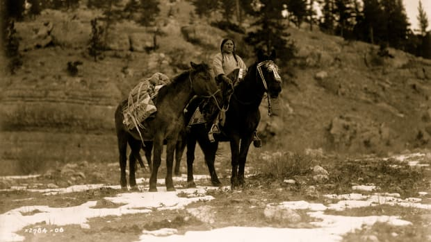 1908: Apsaroke woman on horseback, packhorse beside her.