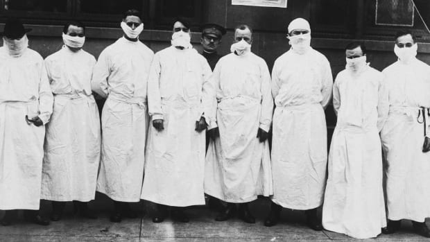 Doctors, army officers, and reporters wear surgical gowns and masks at a hospital to observe Spanish influenza treatment of patients