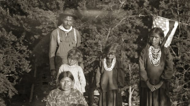 John Mike Jr (HayShooKeekah), rear left, pictured with his family, Black River Falls, Wisconsin, 1901. Standing from left to right are daughters Ada Mike (HunkEWinKah), Lizzie Mike (WeHunKah), and Belle (Mattie) Mike (ENooKah). Wife Kate Mike (ENooKeeKah) is sitting with son Dewey Mike (WaHoPinNeKeKah) in her lap. Dewey Mike, who became an army private, was killed in action on August 30, 1918, in France. A member of Company A, 128th Infantry, he was among the twelve thousand Native Americans on active duty during World War I At the time, most Native Americans were not United States citizens and were not granted citizenship until the passage of the Indian Citizenship Act of 1924. Dewey was honored posthumously in May of 1933 when his mother visited his grave. Kate Mike was the only Native American Gold Star Mother to be invited by the government to visit France. She made the trip despite her limited ability to speak English, laying a wreath of pine boughs from the trees Dewey played beneath when he was a boy on his grave. (Photo by Charles Van Schaick/Wisconsin Historical Society/Getty Images)