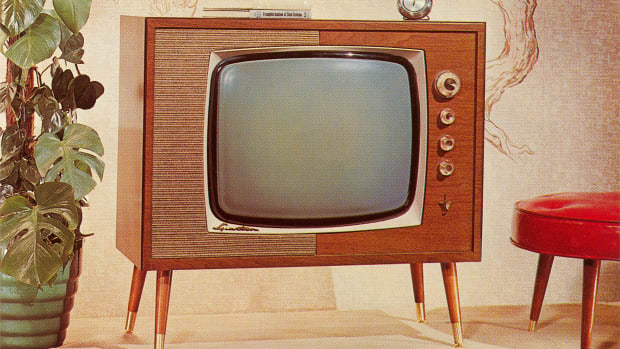 A 1960s-era TV set on legs is shown between a potted plant and red footstool.